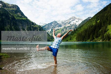Mature man standing in lake, kicking water, Lake Vilsalpsee, Tannheim Valley, Austria