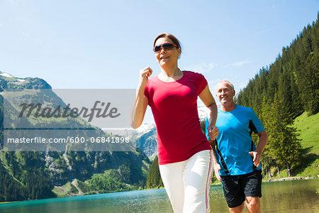 Mature man and woman power walking, Lake Vilsalpsee, Tannheim Valley, Austria