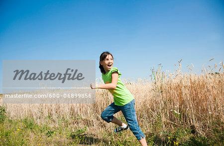Girl running in field on hill, Germany