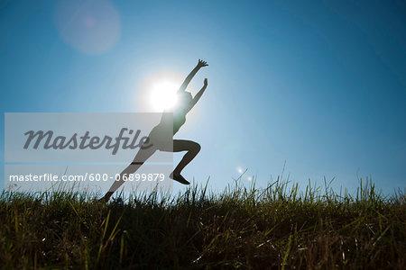 Silhouette of teenaged girl running in field, Germany