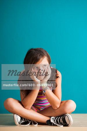 Portrait of girl sitting on floor looking upset, Germany