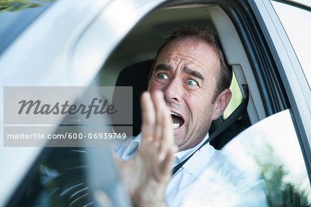 Frightened Businessman Driving Car, Mannheim, Baden-Wurttemberg, Germany