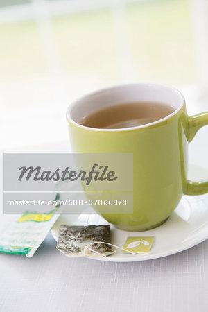 Used Tea Bag on Saucer with Cup of Tea in Green Mug, Studio Shot