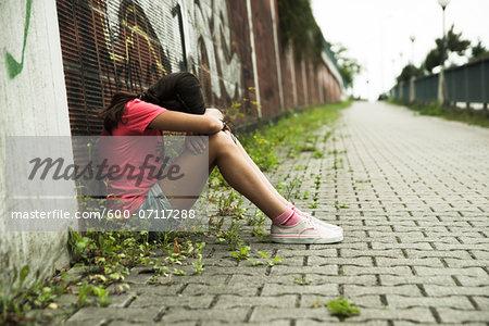Girl Sitting on Ground in Alley, Mannheim, Baden-Wurttemberg, Germany