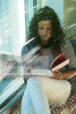 Teenage girl sitting next to window, reading book, Germany