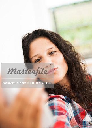Teenage girl posing and taking selfie with smart phone, Germany
