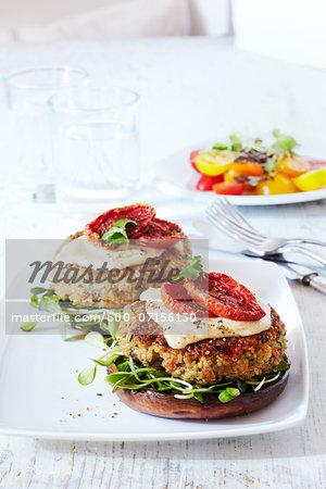 Quinoa veggie burgers on platter, studio shot