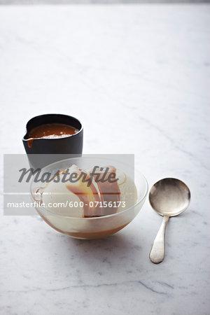 Vanilla Ice Cream with caramel sauce in bowl with spoon, studio shot