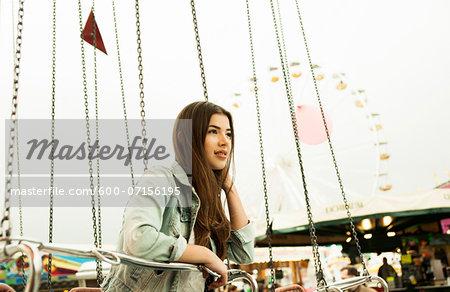 Teenage girl sitting on amusement park ride, Germany