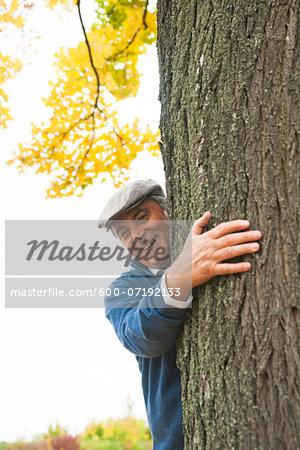 Portrait of Senior Man Standing behind Tree, Mannheim, Baden-Wurttemberg, Germany