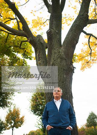 Portrait of Senior Man Leaning Against Tree, Mannheim, Baden-Wurttemberg, Germany