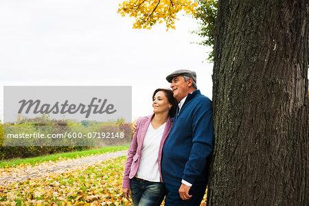 Couple leaning against Tree Trunk, Mannheim, Baden-Wurttmeberg, Germany