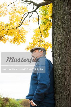 Senior Man leaning against Tree in Autumn, Mannheim, Baden-Wurttemberg, Germany