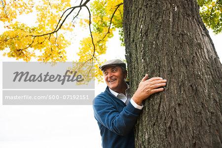 Senior Man Standing behind Tree, Mannheim, Baden-Wurttemberg, Germany