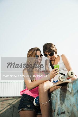 Girls Looking at MP3 Player in Skatepark, Feudenheim, Mannheim, Baden-Wurttemberg, Germany
