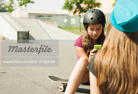 Girls using Cell Phone in Skatepark, Feudenheim, Mannheim, Baden-Wurttemberg, Germany