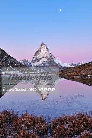 Matterhorn reflected in Lake Riffelsee at Dawn with Moon, Zermatt, Alps, Valais, Switzerland