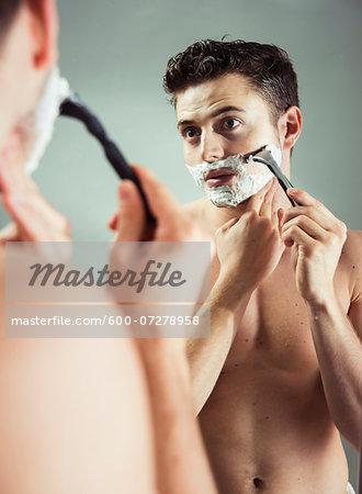 Young man looking in bathroom mirror, shaving with razor, studio shot on grey background