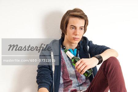 Teenage boy wearing headphones around neck and holding bottle of beer, studio shot on white background