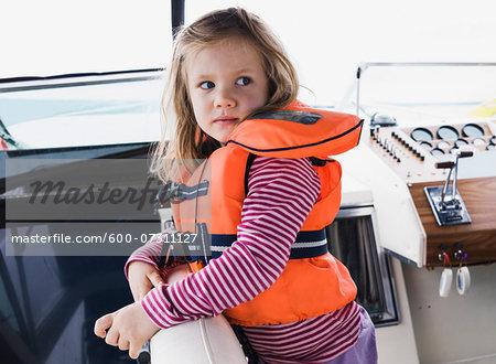 Portrait of 3 year old girl in orange life jacket on a motorboat, Sweden