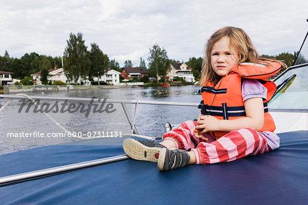 3 year old girl in orange life jacket sitting on top of motorboat, docked on lake, Sweden