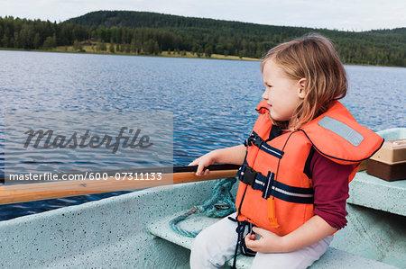 3 year old girl in orange life jacket sitting in a motorboat, fishing, Sweden