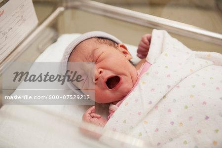 Newborn Baby Girl Yawning in Hospital Bassinet