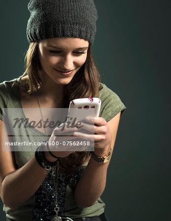 Portrait of Teenage Girl using Cell Phone, Studio Shot