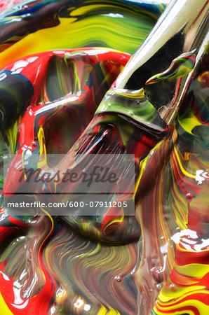 Close-up of paint swirls and brush