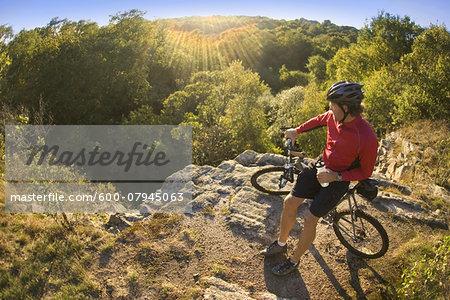 Man on bicycle taking a water break while mountain biking through Ballard Park in Newport, Rhode Island, USA
