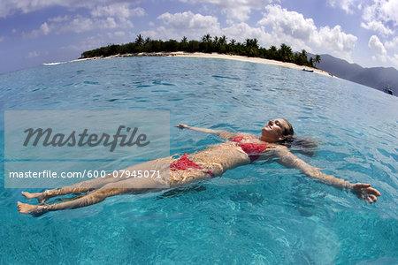 Woman floating in the Caribbean Sea at Little Jost Van Dyke in the British Virgin Islands, Caribbean
