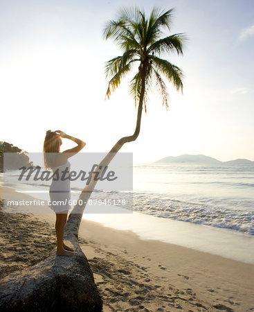 Woman standing on palm tree on beach with sun, Cane Garden Bay, Tortola, Caribbean