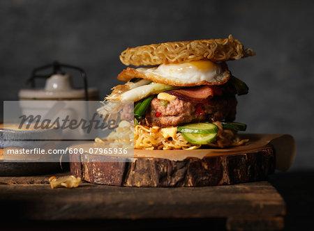 Ramen burger with fried egg, aioli sauce, cucumbers, leeks and bacon.