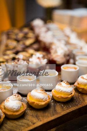 Lemon Meringue Tarts and Cups of Creme Brulee on Dessert Table at Wedding Reception