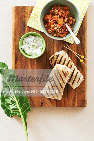 Chickpea and swiss chard burrito with yogurt dip on a cutting board, studio shot