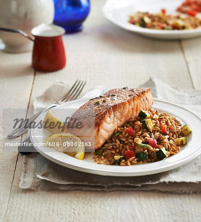 Seared Salmon with grain pilaf and lemons on a plate, studio shot