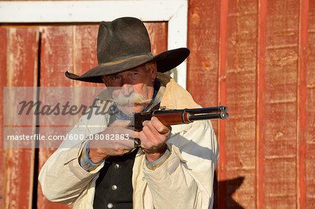 Portrait of Cowboy Aiming Rifle, Shell, Wyoming, USA