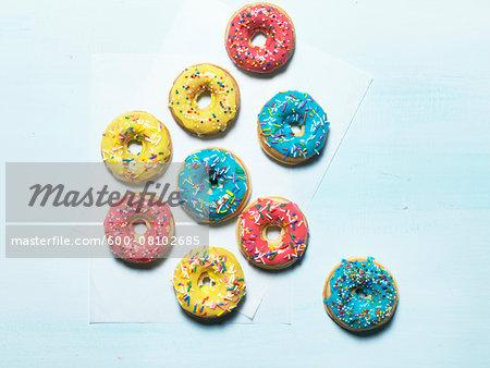 Multicoloured sprinkled donuts, studio shot on blue background