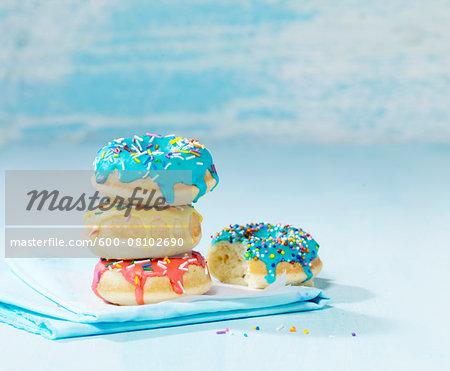 Stack of multicoloured sprinkled donuts with blue napkin, studio shot on blue background