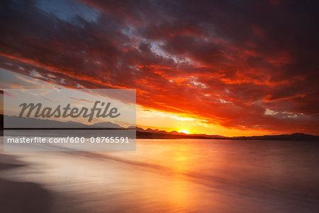 Dramatic red sunset at Cala Sabina Beach in Golfo Aranci in the Province of Sassari in Sardinia