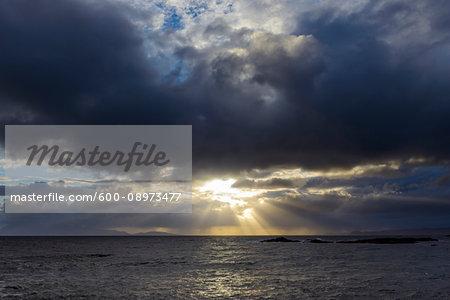 Sun shining through the storm clouds at sunrise along the Scottish coast at Mallaig in Scotland, United Kingdom