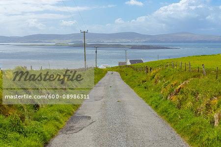 Single track road through coastal landscape on the Isle of Skye in Scotland, United Kingdom