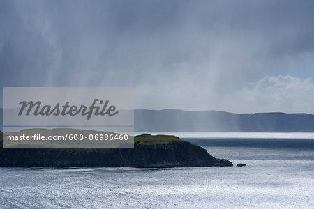 Sunlit sea cliffs and rainclouds along the coast of the Isle of Skye in Scotland, United Kingdom
