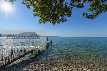 Sun shining on Lake Garda (Lago di Gardo) with wooden jetty in the summer at Garda in Veneto, Italy