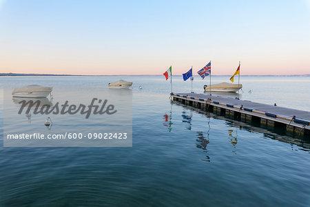 Covered, motorboats docked at jetty at dawn on Lake Garda (Lago di Garda) at Bardolino in Veneto, Italy