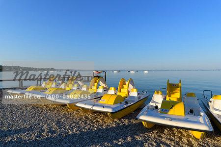 Row of colorful pedal boats on the beach in the morning at Lake Garda (Lago di Garda) in Bardolino in Veneto, Italy