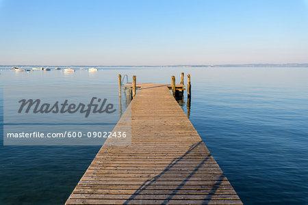 Wooden jetty on Lake Garda (Lago di Garda) on a sunny morning at Bardolino in Veneto, Italy