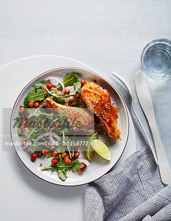 Maple chcken dumsticks with sald on dinner plate