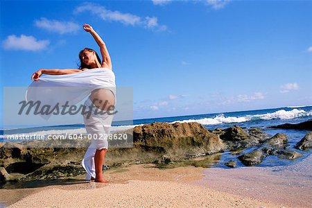 Pregnant woman dancing on beach