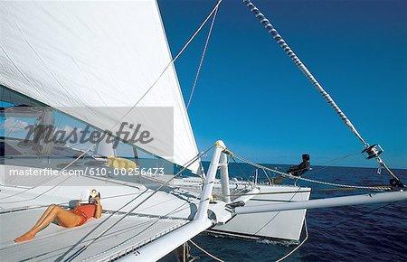 Virgin Islands, woman sunbathing on cruising catamaran
